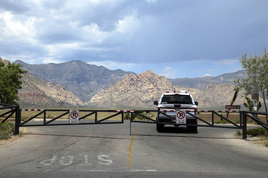 A Bureau of Land Management ranger blocks the entrance to the Red Rock Overlook on U.S. Highway ...