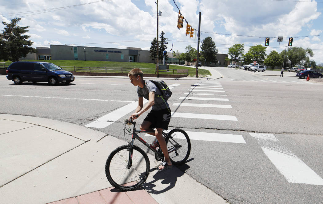 A bicyclist rides away from Columbine High School, Thursday, June 13, 2019, in Littleton, Colo. ...