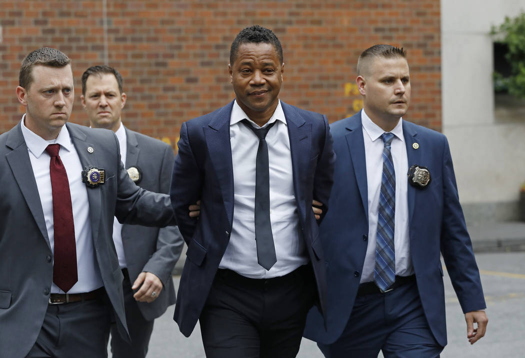 Actor Cuba Gooding Jr., center, is lead by police officers from the New York Police Department' ...