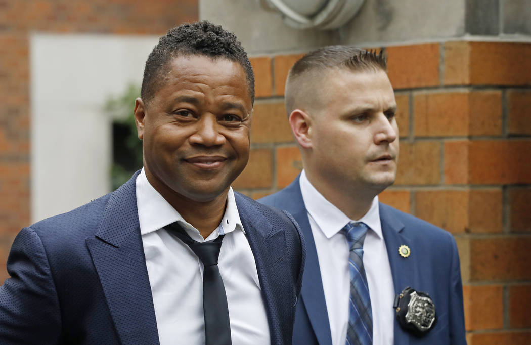 Actor Cuba Gooding Jr., left, is lead by a police officer from New York's Special Victim's Unit ...