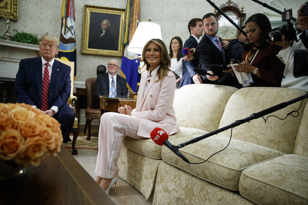 President Donald Trump looks on as first lady Melania Trump talks with reporters during a meeti ...