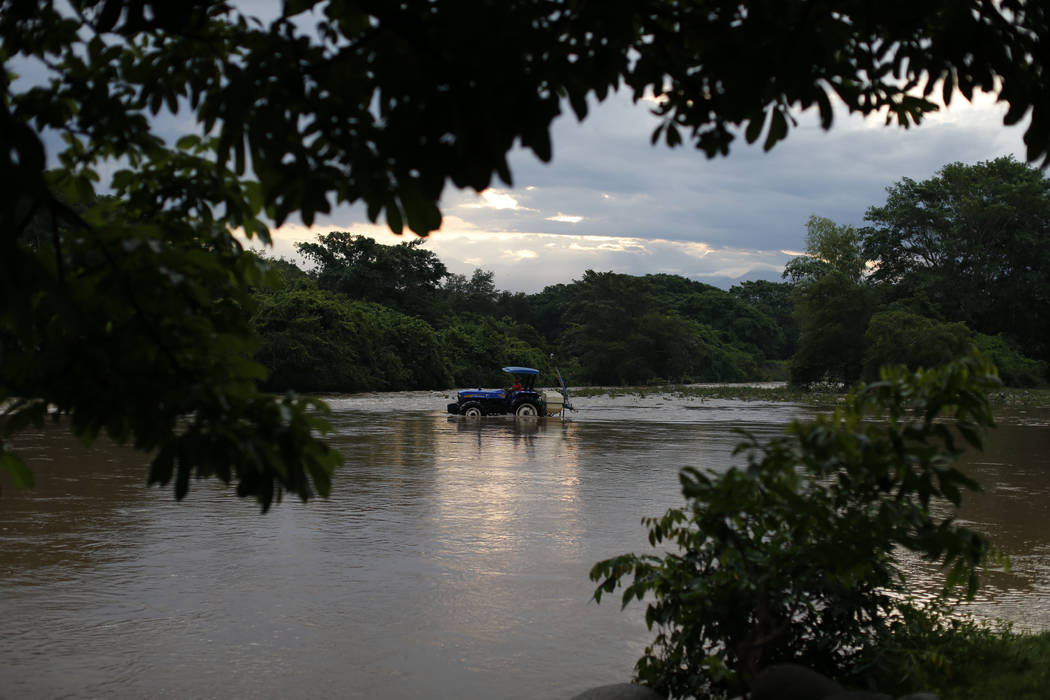 A man drives a tractor through the Suchiate river from Frontera Hidalgo, Mexico, toward Guatema ...