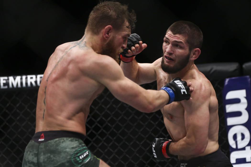 Conor McGregor, left, fights Khabib Nurmagomedov during their lightweight title bout at UFC 229 ...