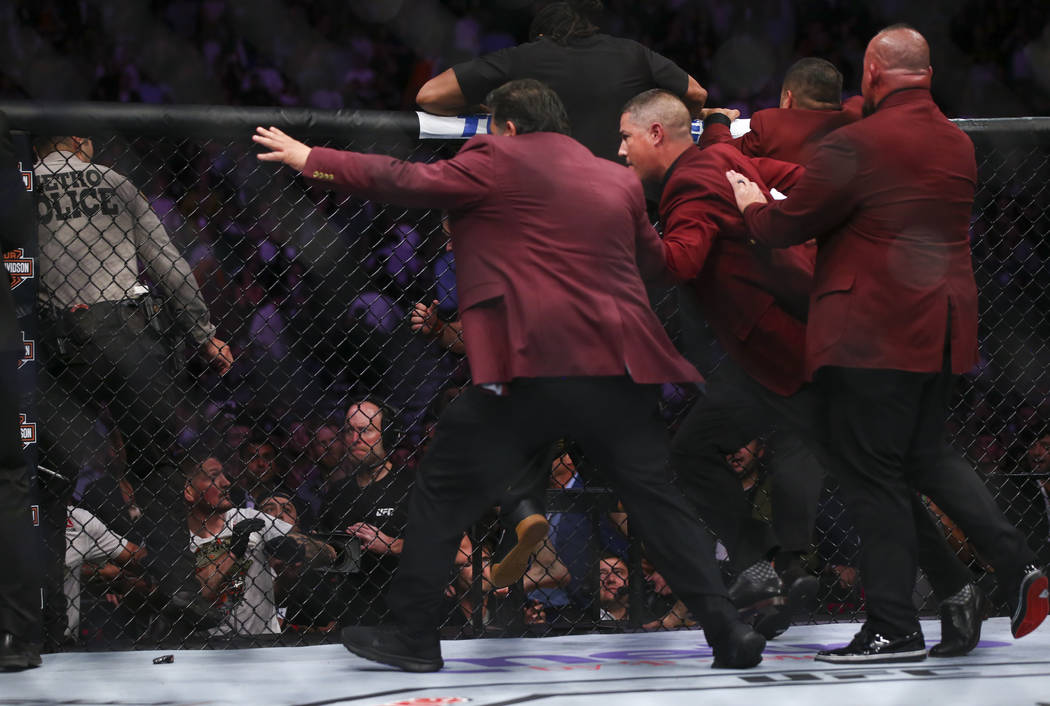 Members of security chase after Khabib Nurmagomedov after he jumped out of the octagon followin ...