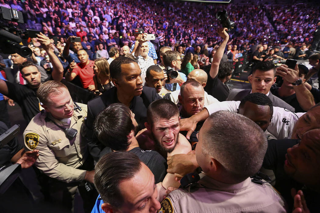 Khabib Nurmagomedov is restrained outside of the octagon after he defeated Conor McGregor at UF ...