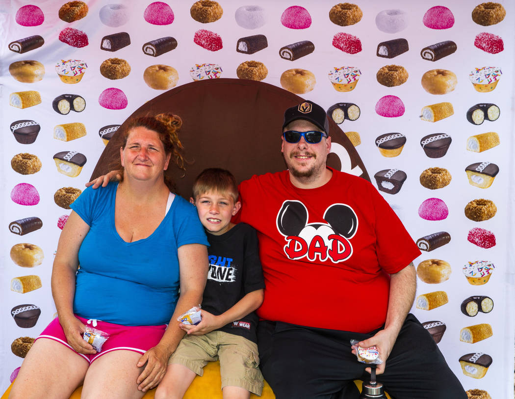 Mary Pfeiffer and son Tristan, 9, join Chris Orando in a photo atop a giant Twinkie while on a ...