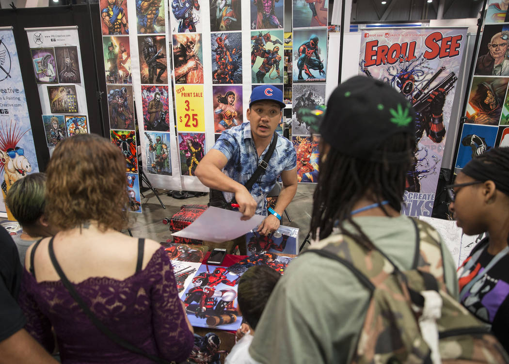 Artist Eroll See, center, sells prints during the Amazing Las Vegas Comic Con on Friday, June 1 ...