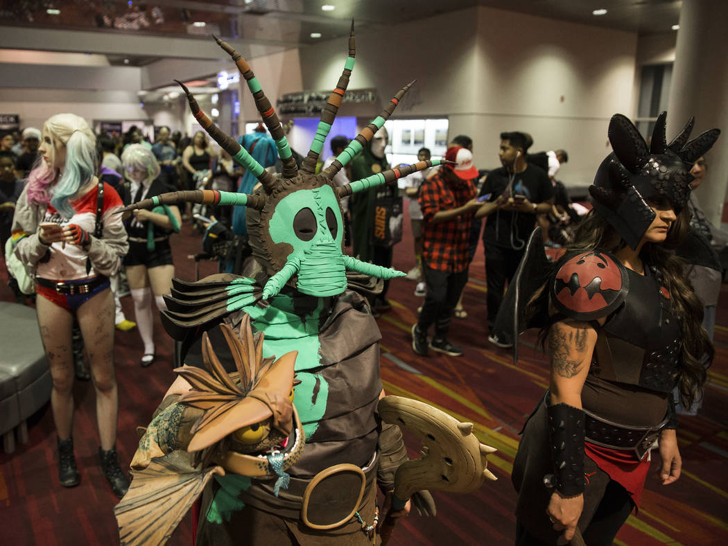 """Robin Hampton, left, dressed as a character in """"How to Train Your Dragon,"""" waits in line to ent ..."""