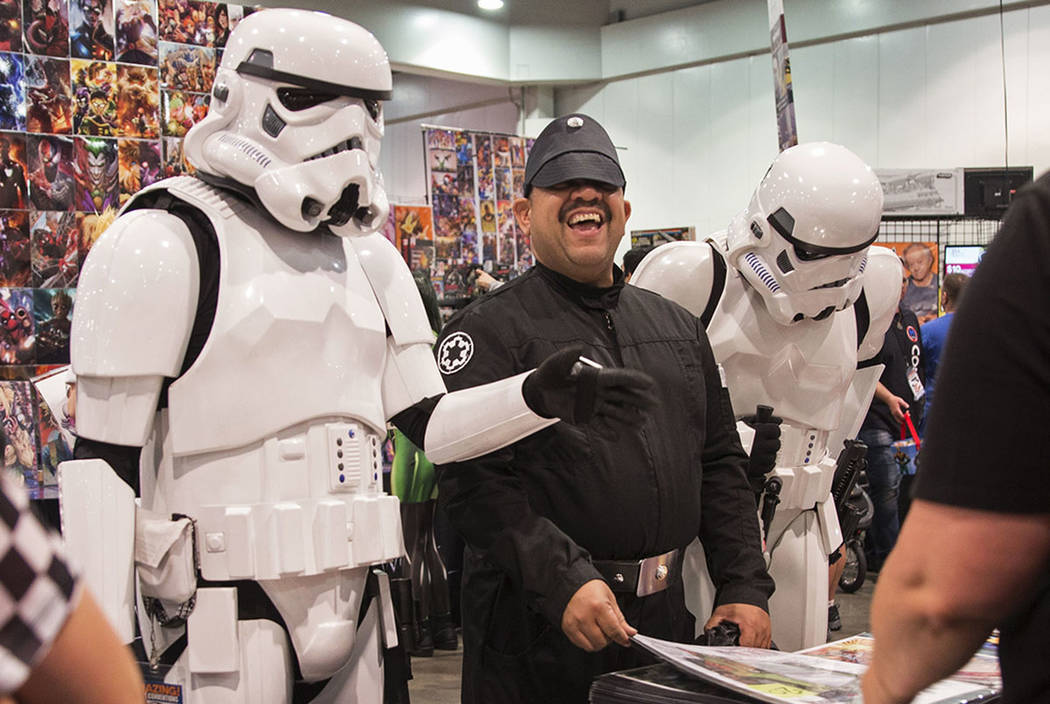 Jathniel Velazquez, center, shares a laugh with a pair of stormtroopers while looking at comic ...