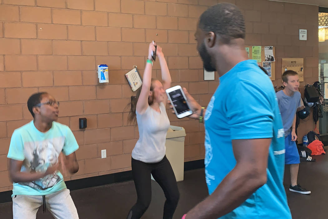 Courtney Woods encourages teens performing jumping jacks during his Power Hour class at the Sky ...