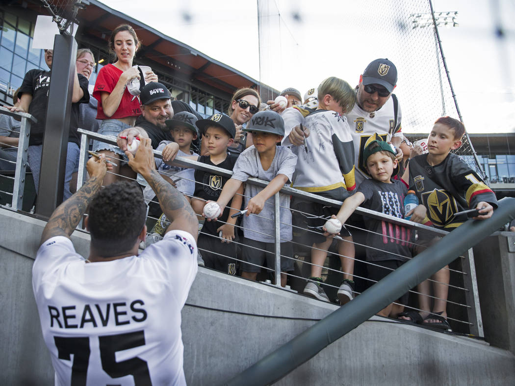 Golden Knights right wing Ryan Reaves, left, signs autographs before the start of the Battle Fo ...