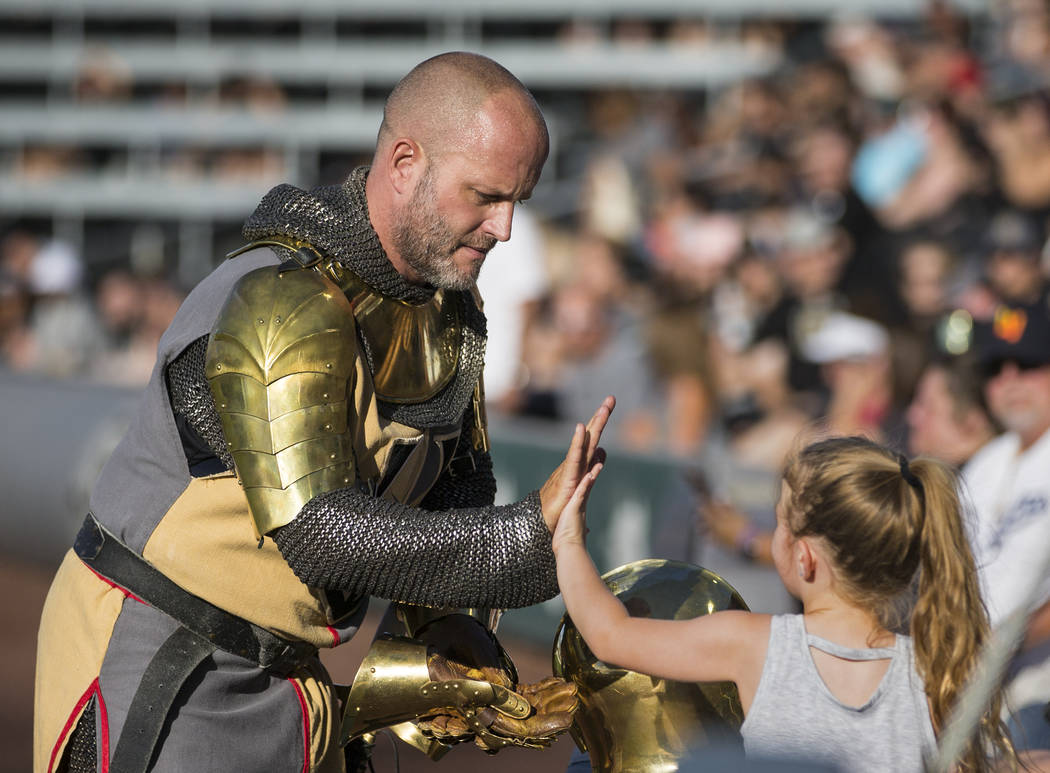 Lee Orchard, aka The Golden Knight, left, high fives a fan during the Battle For Vegas Charity ...