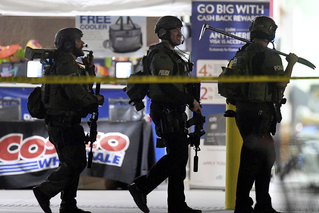 Heavily armed police officers exit the Costco following a shooting inside the wholesale warehou ...
