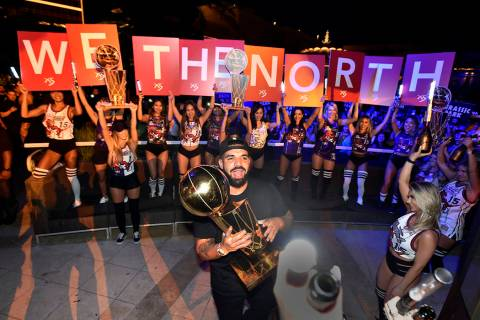 LAS VEGAS, NEVADA - JUNE 14: Drake carries the Larry O'Brien NBA Championship Trophy as he cele ...