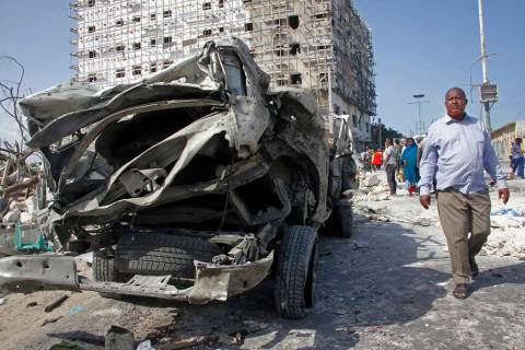 A man walks past the wreckage of an official vehicle that was destroyed in a bomb attack in the ...