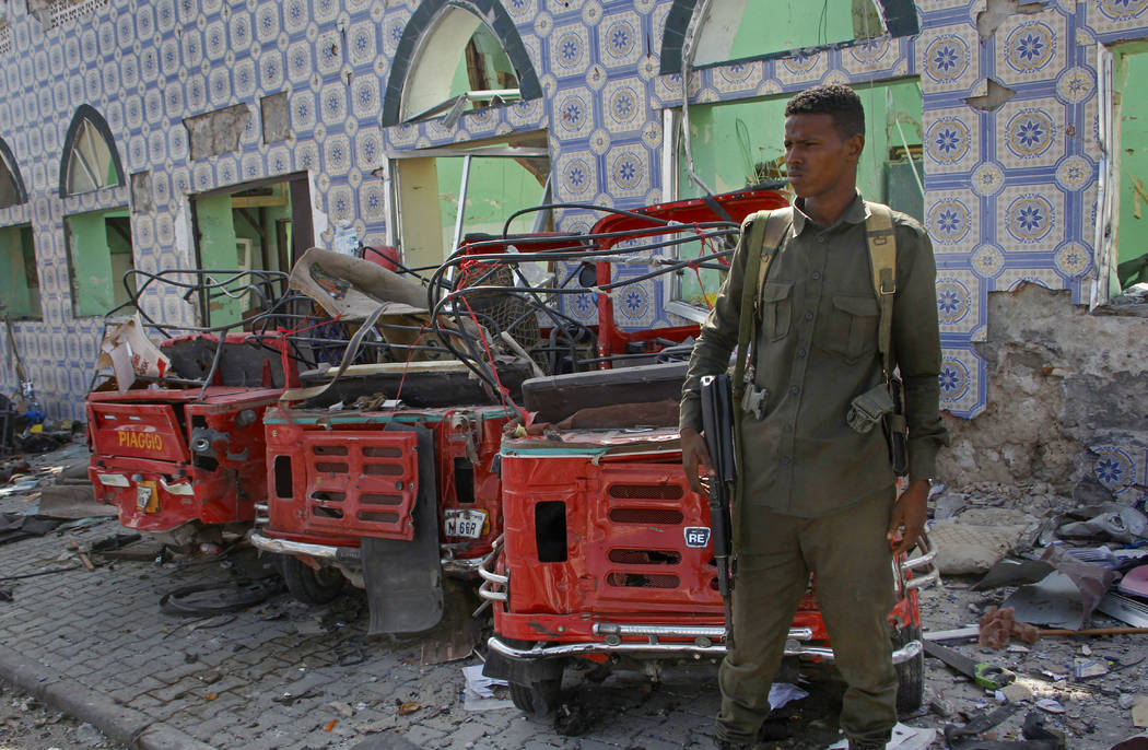 Security forces stand near the wreckage of three-wheeled vehicles destroyed in a bomb attack in ...