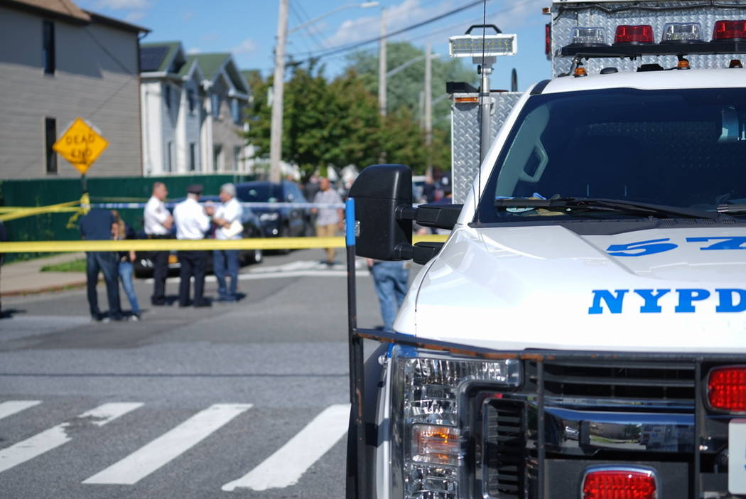 New York City Police officials gather along Wilcox Street behind the 121st Precinct station hou ...