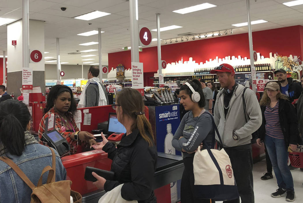 Customers wait on a long check out line at a Target store in San Francisco on Saturday, June 15 ...