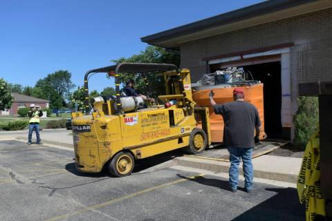 In this Monday, June 10, 2019 photo, workers removed the 12,000 pound open MRI machine from a h ...