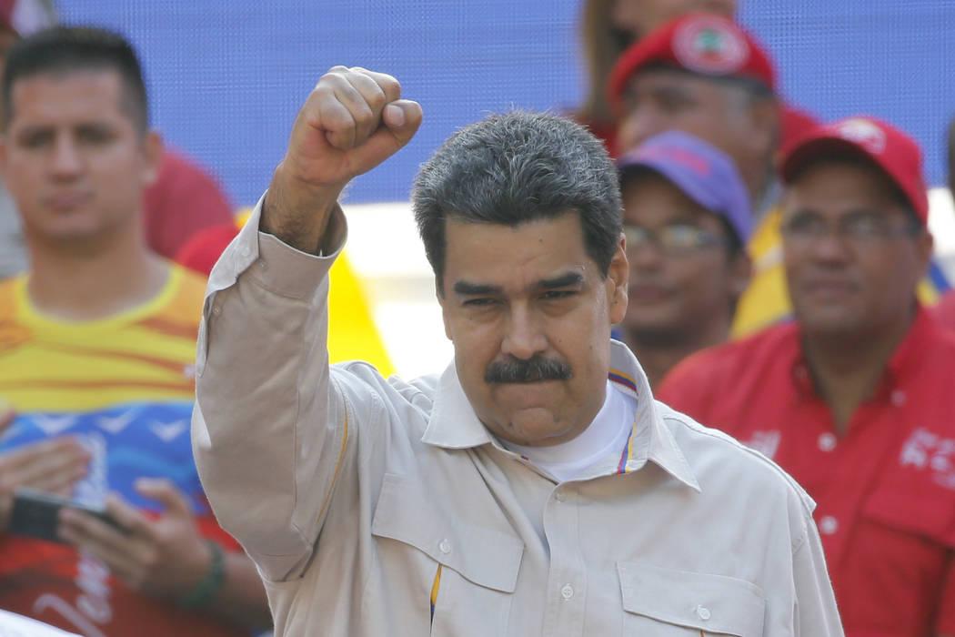 FILE - In this April 6, 2019 file photo, Venezuela's President Nicolas Maduro raises his fist t ...