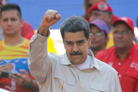 FILE - In this April 6, 2019 file photo, Venezuela's President Nicolas Maduro raises his fist t ...