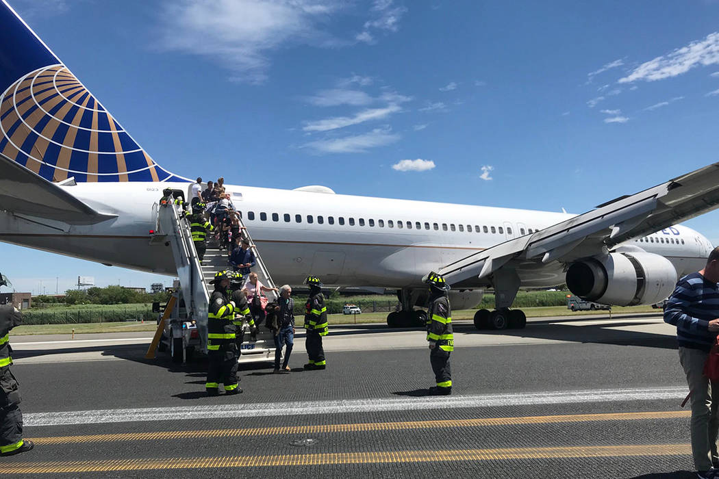 This photo provided by Caroline Craddock shows emergency personnel help passengers off a plane ...