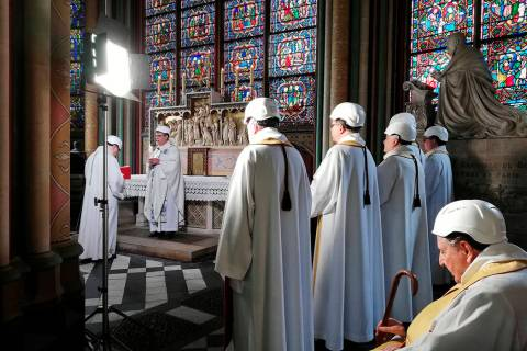 The Archbishop of Paris Michel Aupetit, second left, leads the first mass in a side chapel, two ...