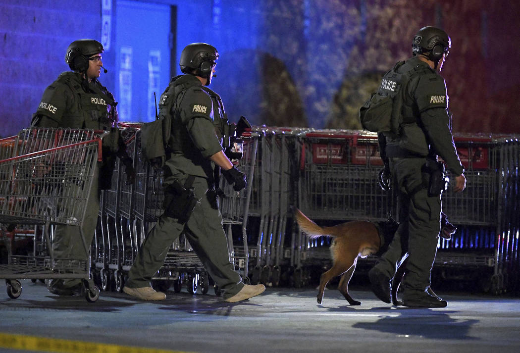 Heavily armed police officers exit the Corona Costco following a shooting inside the wholesale ...