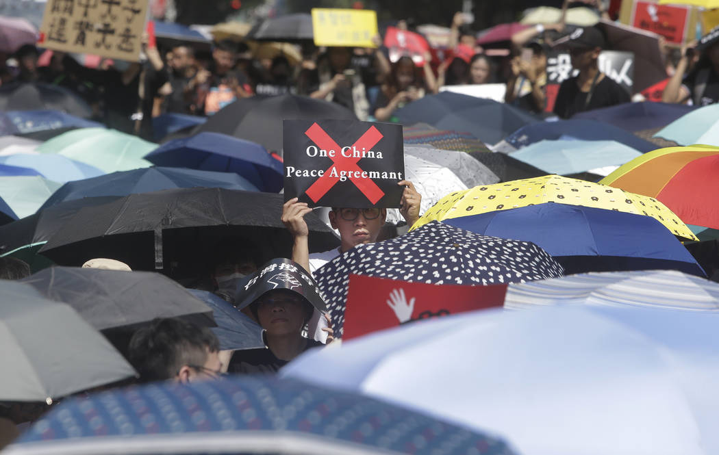 A supporter holds a slogan to oppose the Hong Kong extradition law outside of the Legislative Y ...