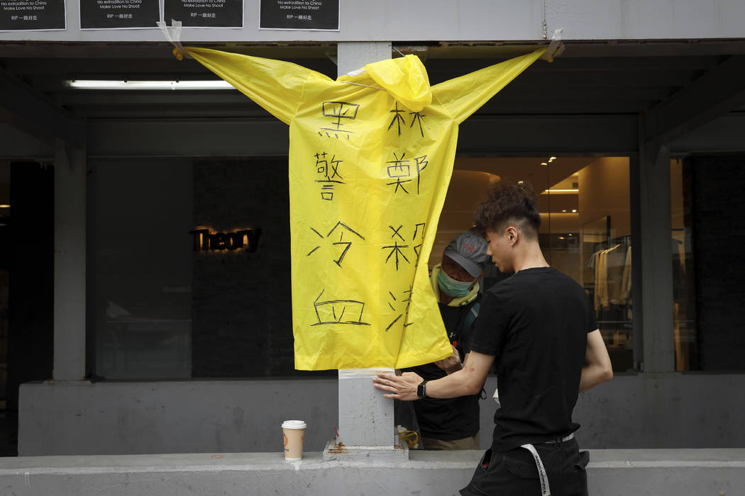 """Protesters place a raincoat bearing the words """"Cold blooded black police, Carrie Lam kill ..."""