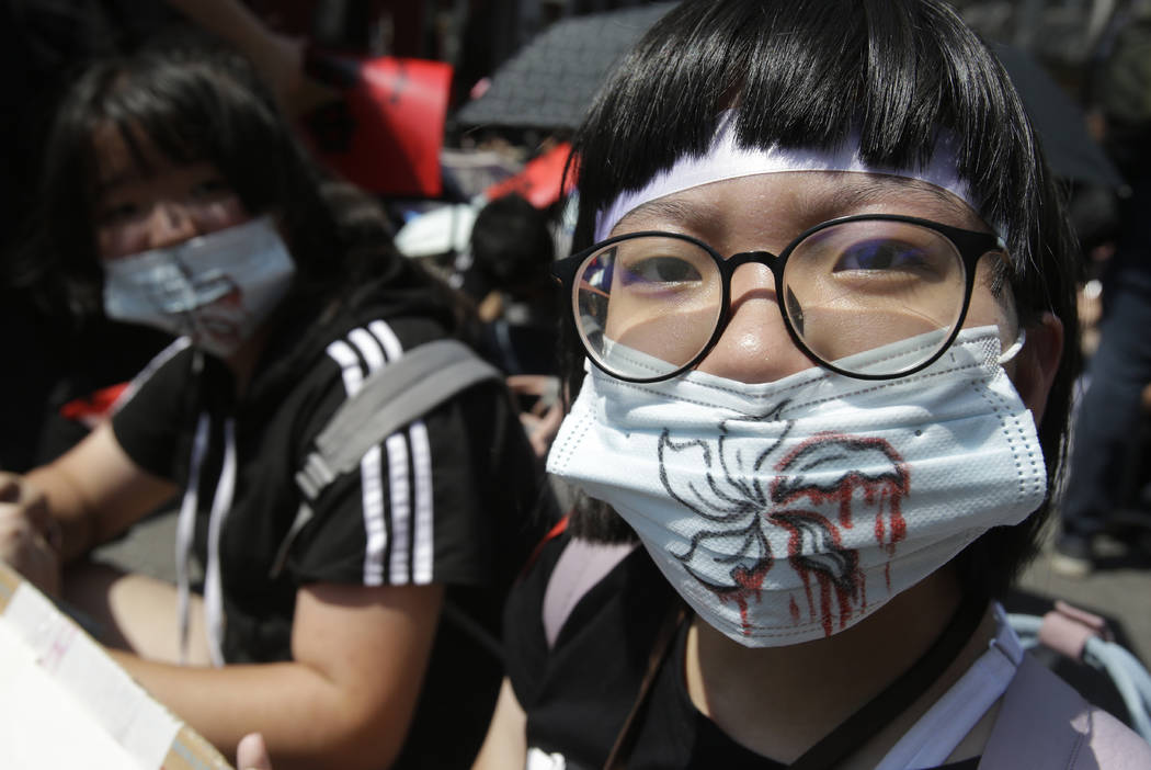 Supporters wear masks with bloody flowers painting for mourning to proposed extradition bill ou ...