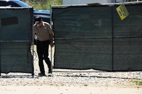 A security guard closes a gate at the construction site of a new clinic that is being built by ...