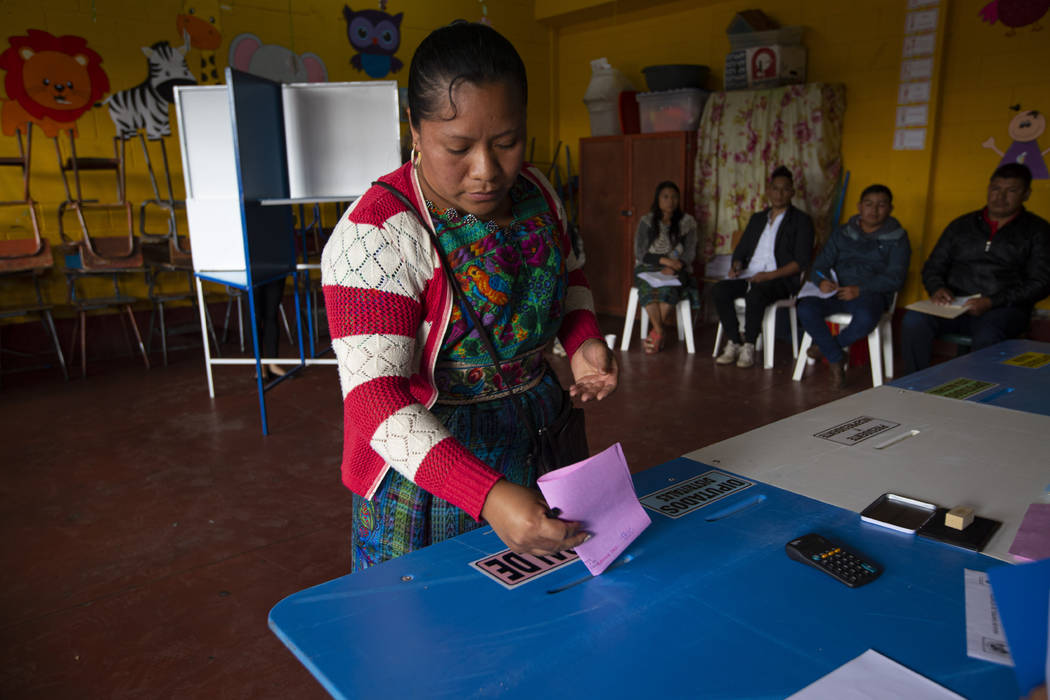 A indigenous woman casts her votes at a polling station in Sumpango, Guatemala, Sunday, June 16 ...