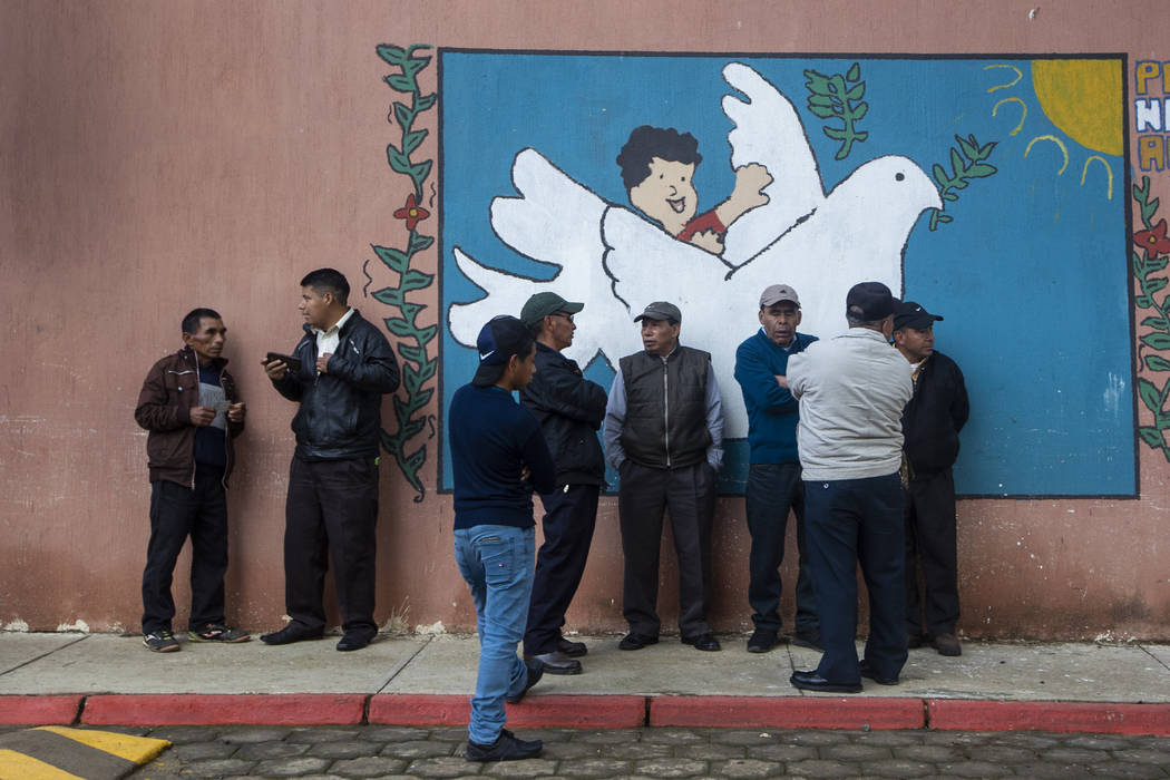 People line up to vote at a polling station in Sumpango, Guatemala, Sunday, June 16, 2019. Guat ...