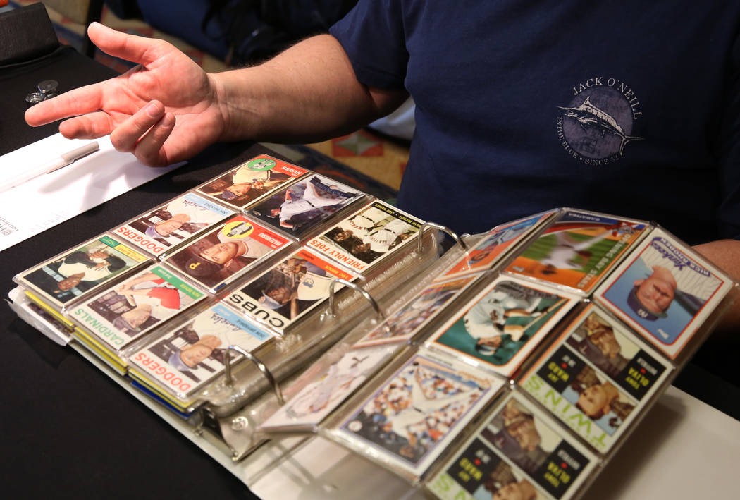 Brian Marcy, owner of Scottsdale Baseball Cards, inspects valuable sports cards on Friday, Jun ...