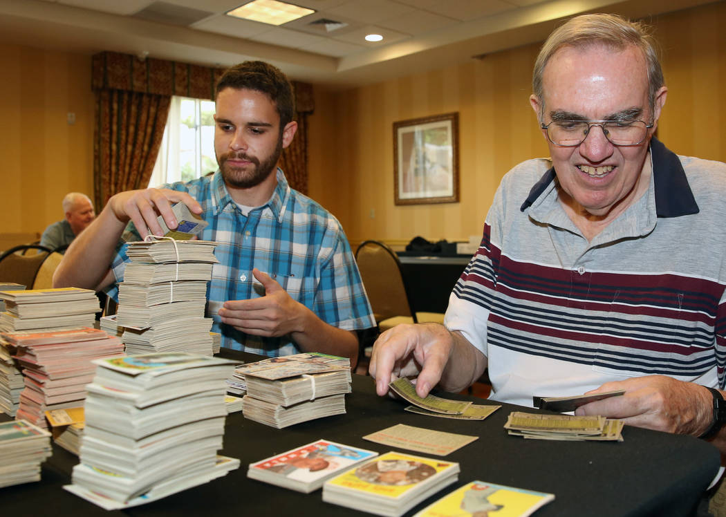 Reuben Lewin, left, and Glenn Sulser, sports cards appraisers, sort out valuable sports cards o ...