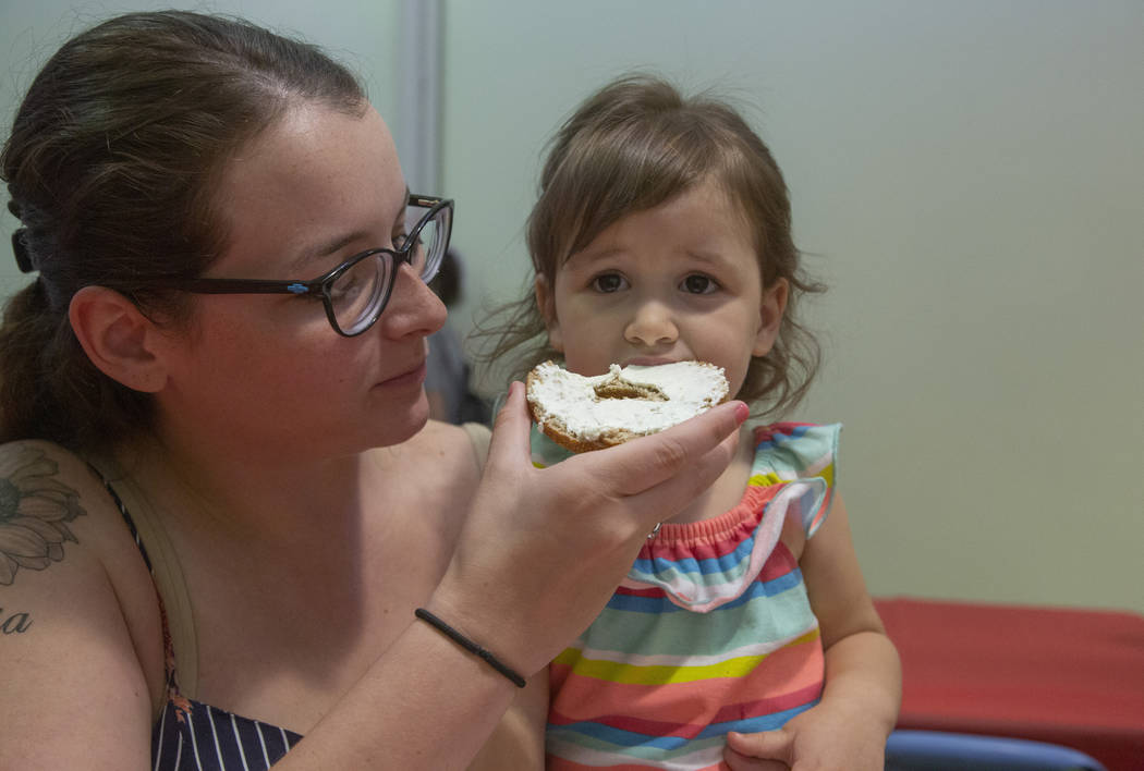 Savannah Castanon of Las Vegas feeds a bagel to her daughter Emilia, 3, during an event to cele ...