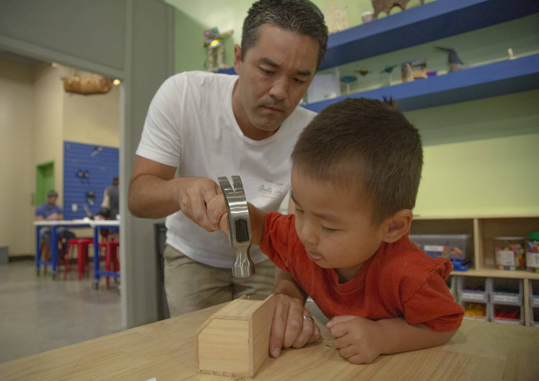 Garrett Clanin, 37, from Hawaii and Kai Clanin, 3, fix a wooden figure during an event to celeb ...