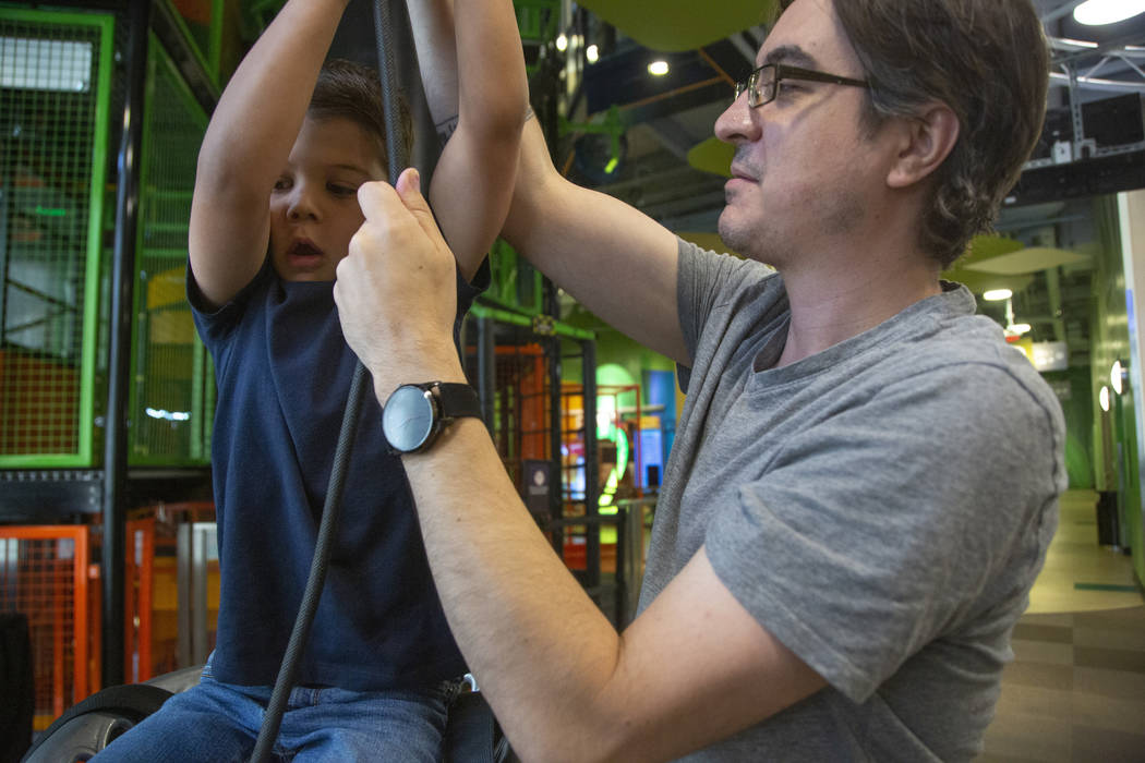 Darren Trentacoste of Las Vegas pulls his son, Lucious, 5, up a ride during an event to celebra ...