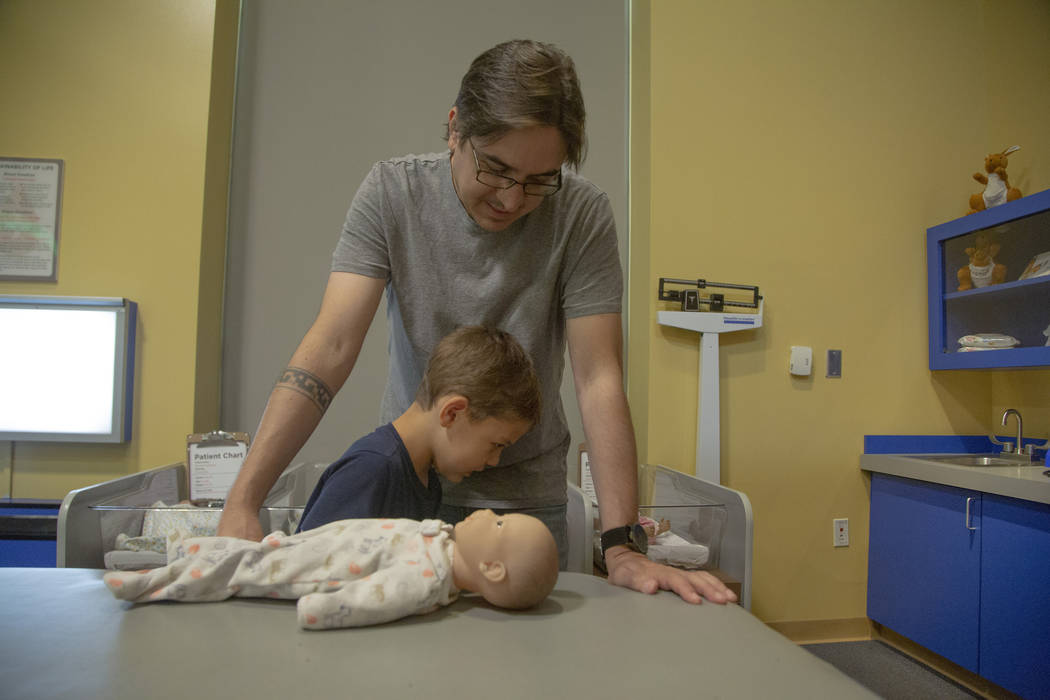 Darren Trentacoste, watches as his son Lucious, 5, learn how to pamper a baby doll at Discovery ...