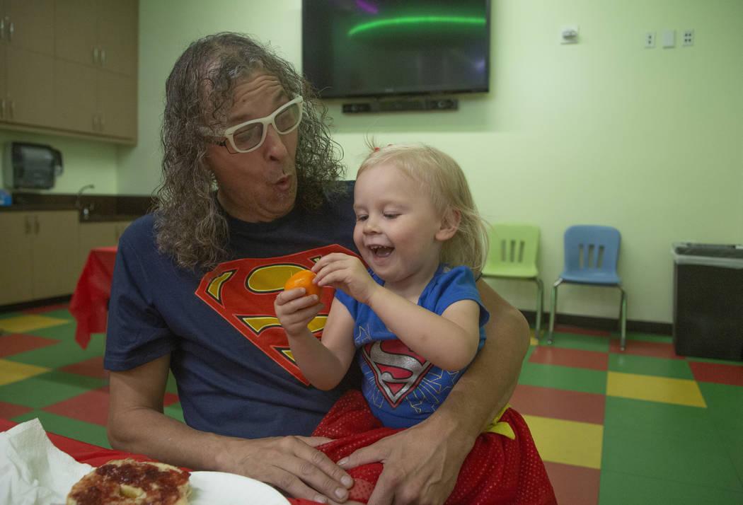 Chris Guzman of Las Vegas laughs with his granddaughter Jazz Lapare- Guzman, 3, during an event ...