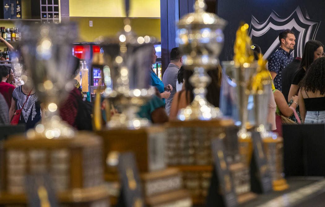 Golden Knights player Mark Stone looks to the line of fans with NHL trophies on display across ...
