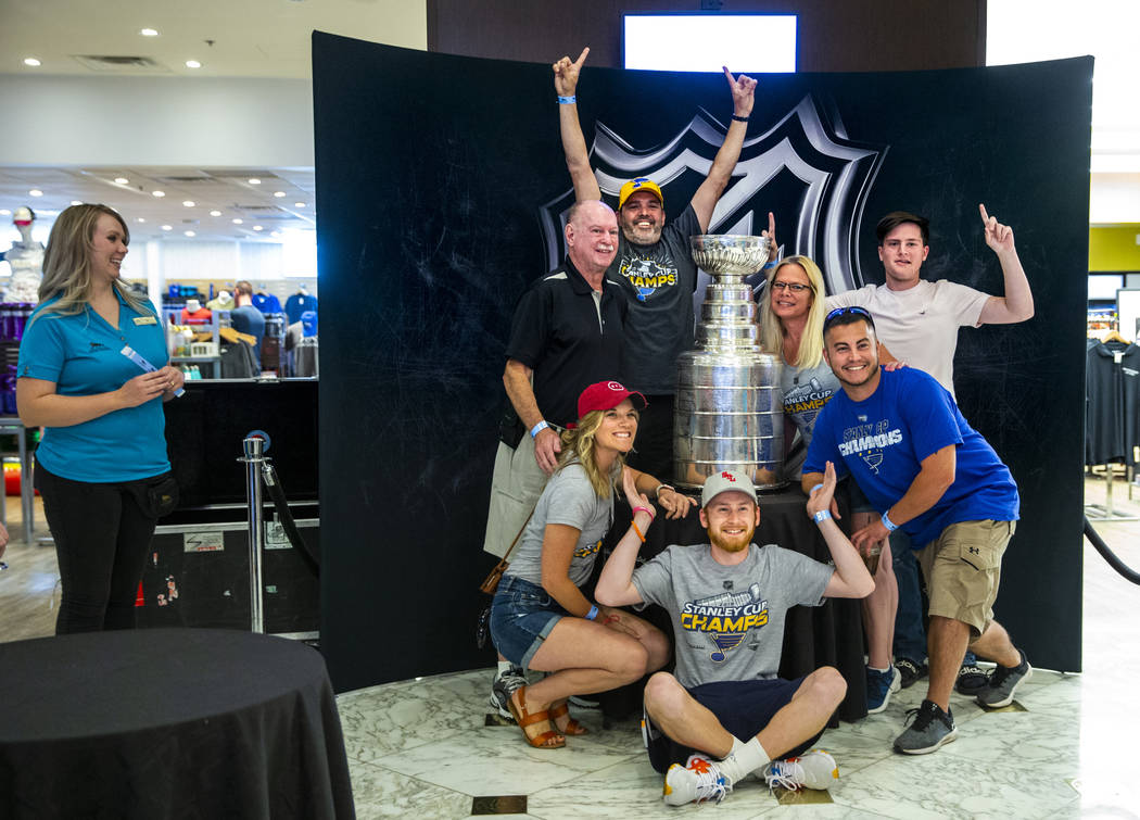 St. Louis Blues fans from the city pose about the Stanley Cup, the most recognizable and revere ...