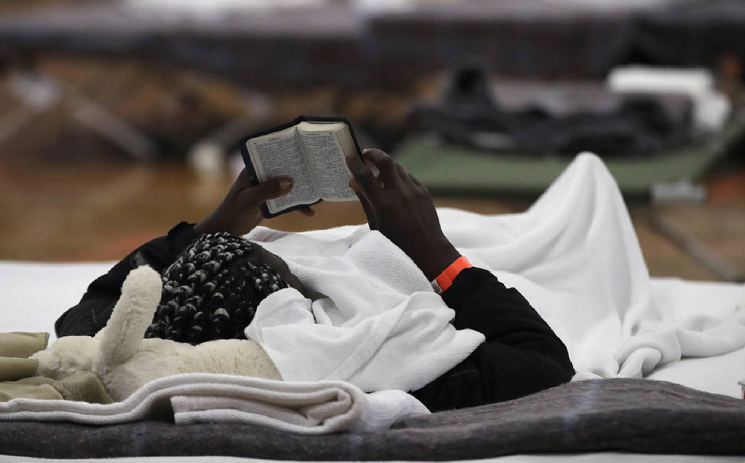A migrant woman reads a Bible as she rests inside the Portland Exposition Building in Portland, ...