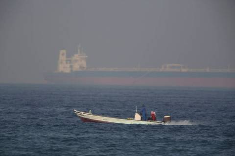 A fishing boat speeds past an oil tanker in the distance in Fujairah, United Arab Emirates, Sat ...