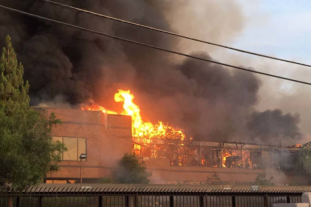 Heavy smoke and flames rise from a fire at a business complex near Paradise Road and East Twain ...