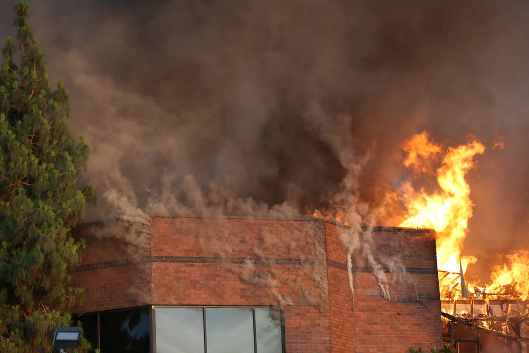 Heavy smoke and flames rise from a fire at at business complex near Paradise Road and East Twai ...