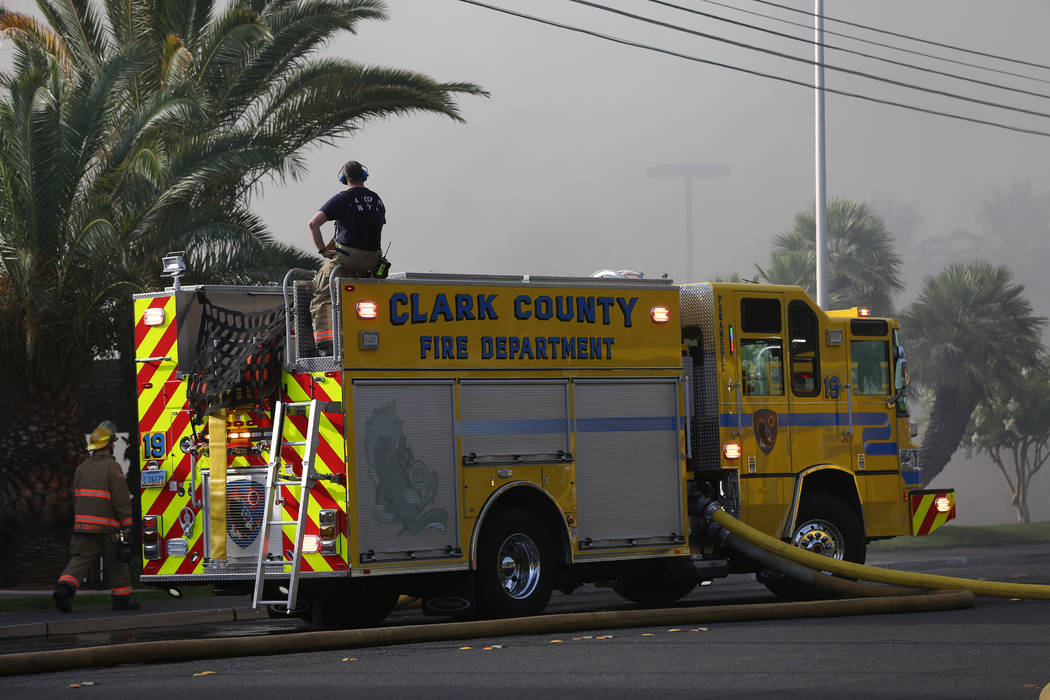 A firefighter watches from atop a Clark County Fire Department truck as an early morning fire e ...