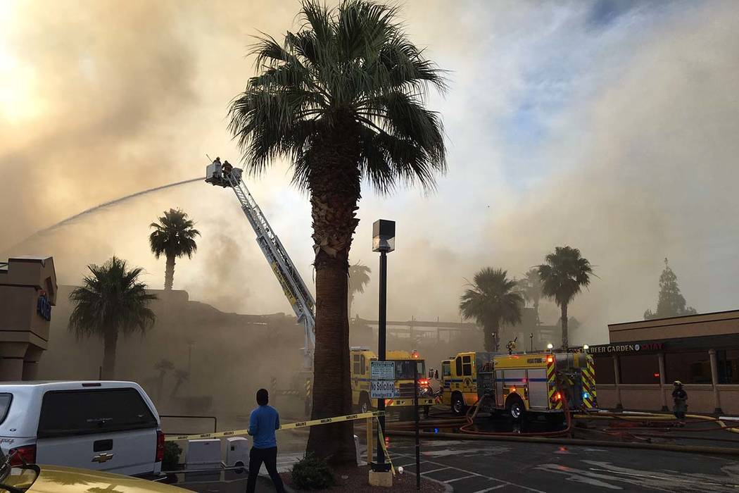 Heavy smoke from a fire surrounds a business complex near Paradise Road and East Twain Avenue i ...
