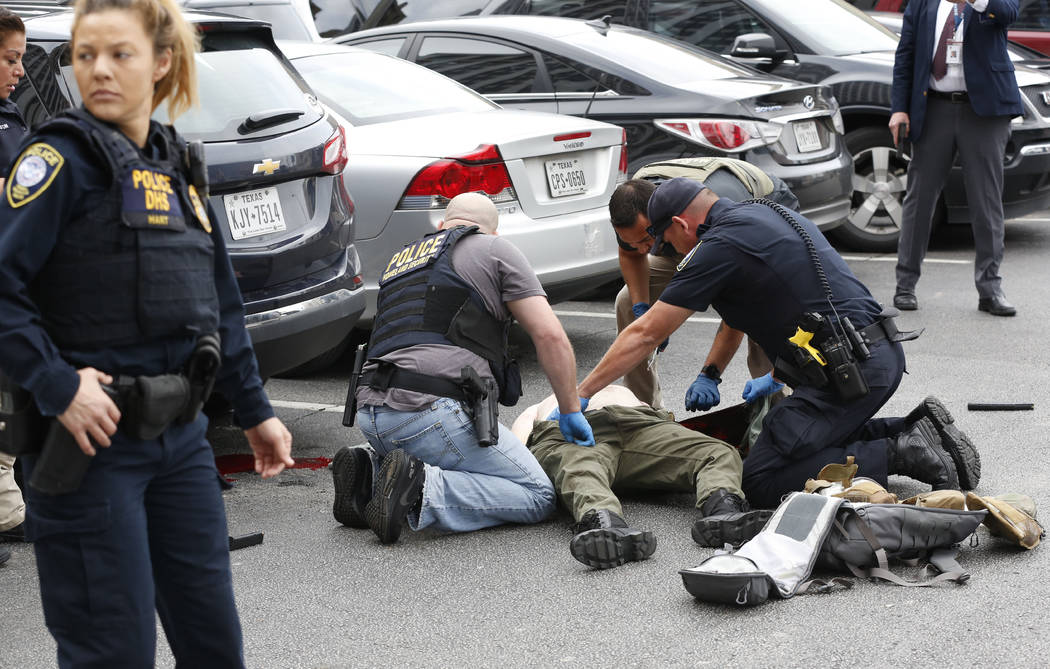 Law enforcement officers attend to an injured shooter in a parking lot after he fired shots at ...
